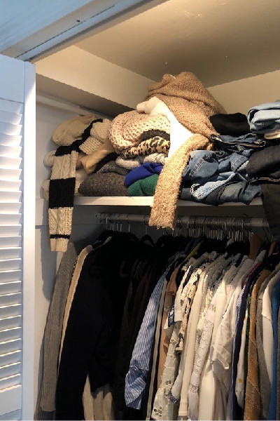 messy closet with sweaters and tops