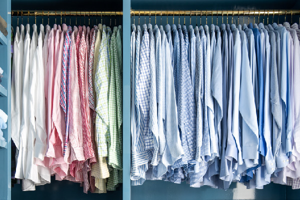 color coded button downs hanging in a closet