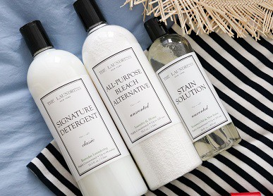 3 laundress products on stripped cotton shirt and straw hat